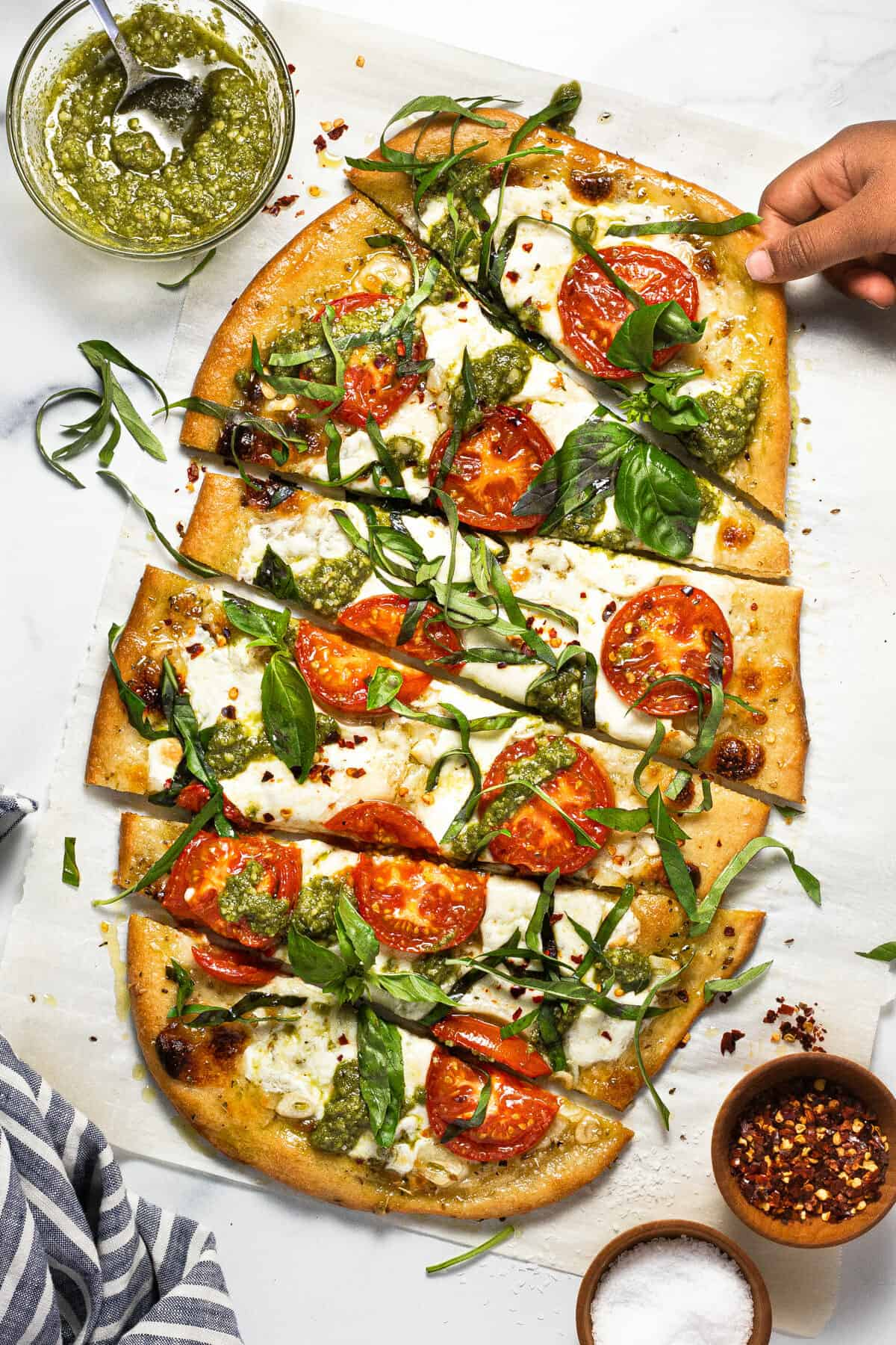 Small hand reaching for a slice of margherita flatbread pizza garnished with basil