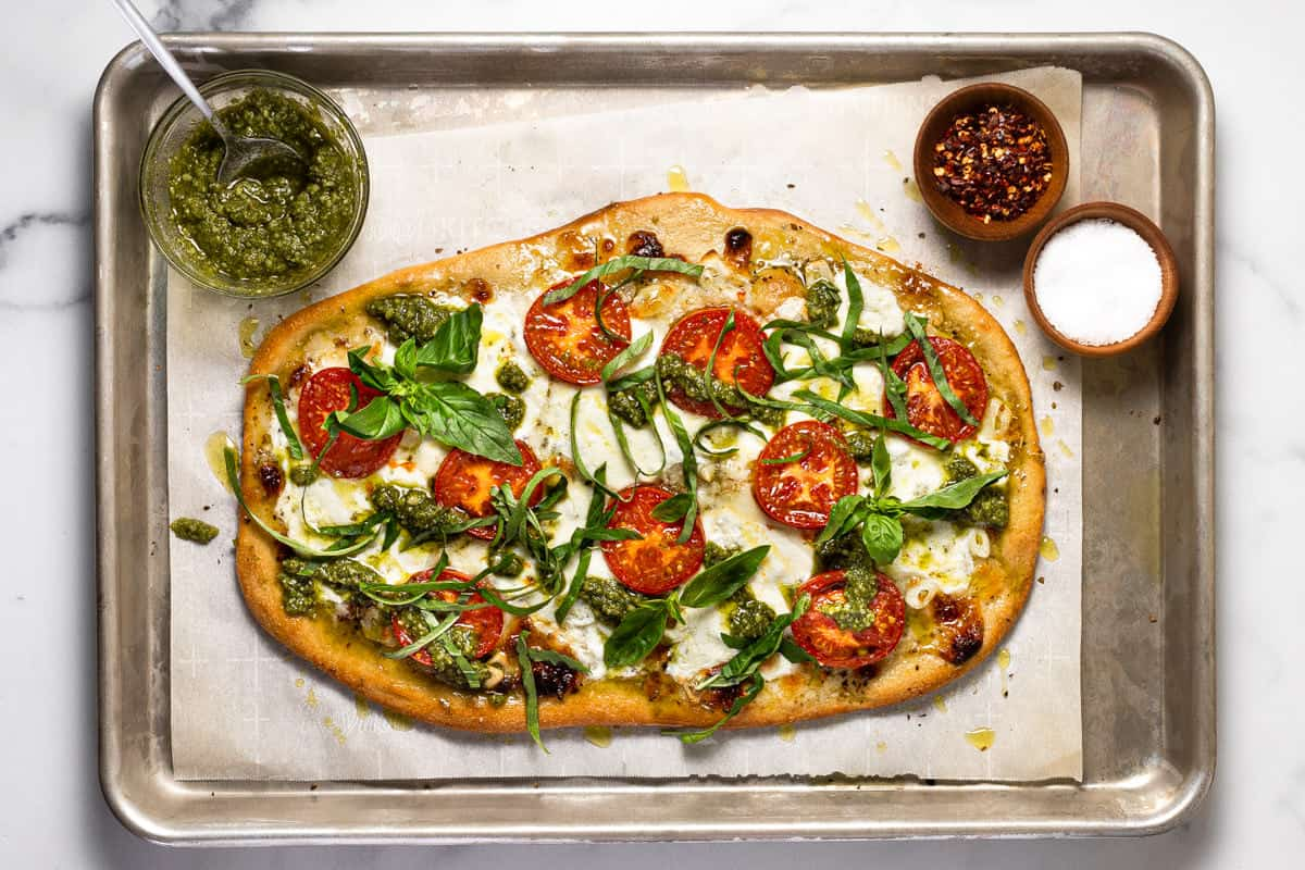 A baking sheet with sliced margherita flatbread pizza garnished with basil