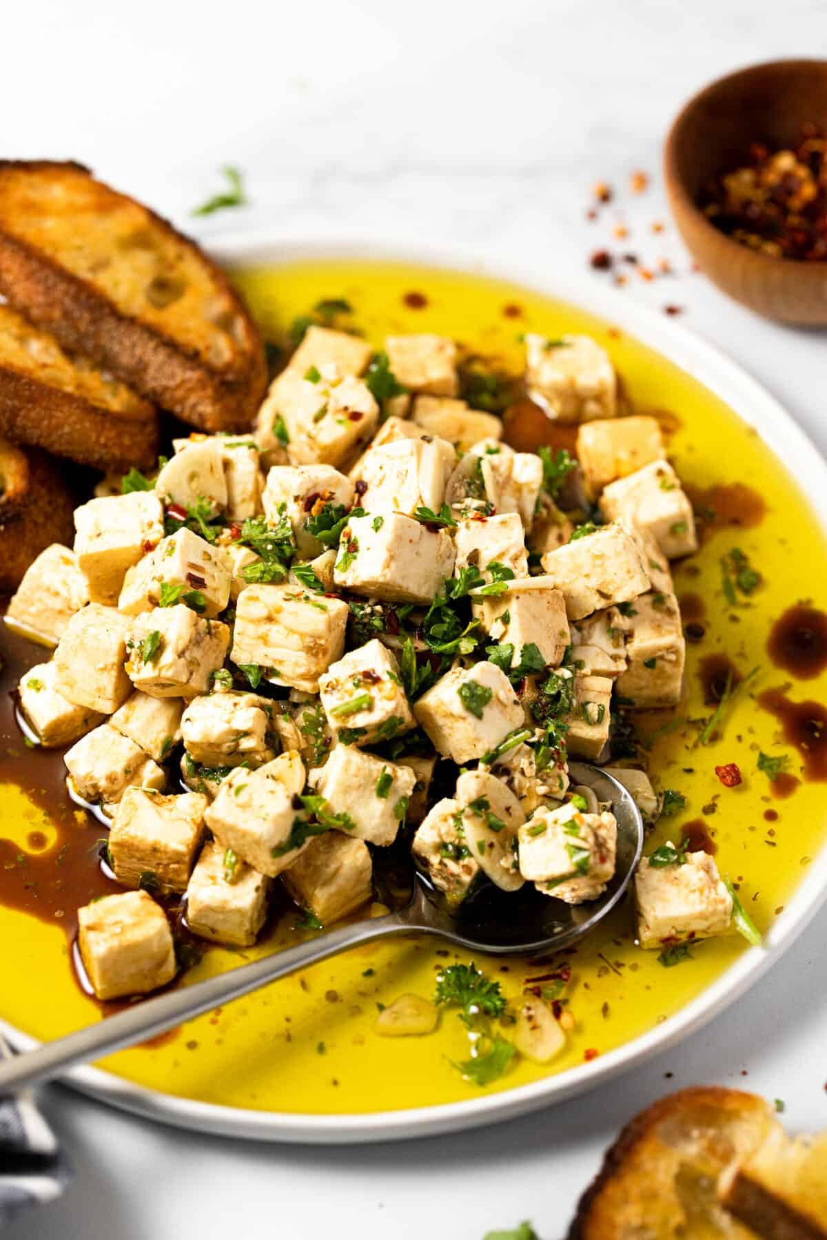 White plate filled with marinated squares of feta garnished with parsley