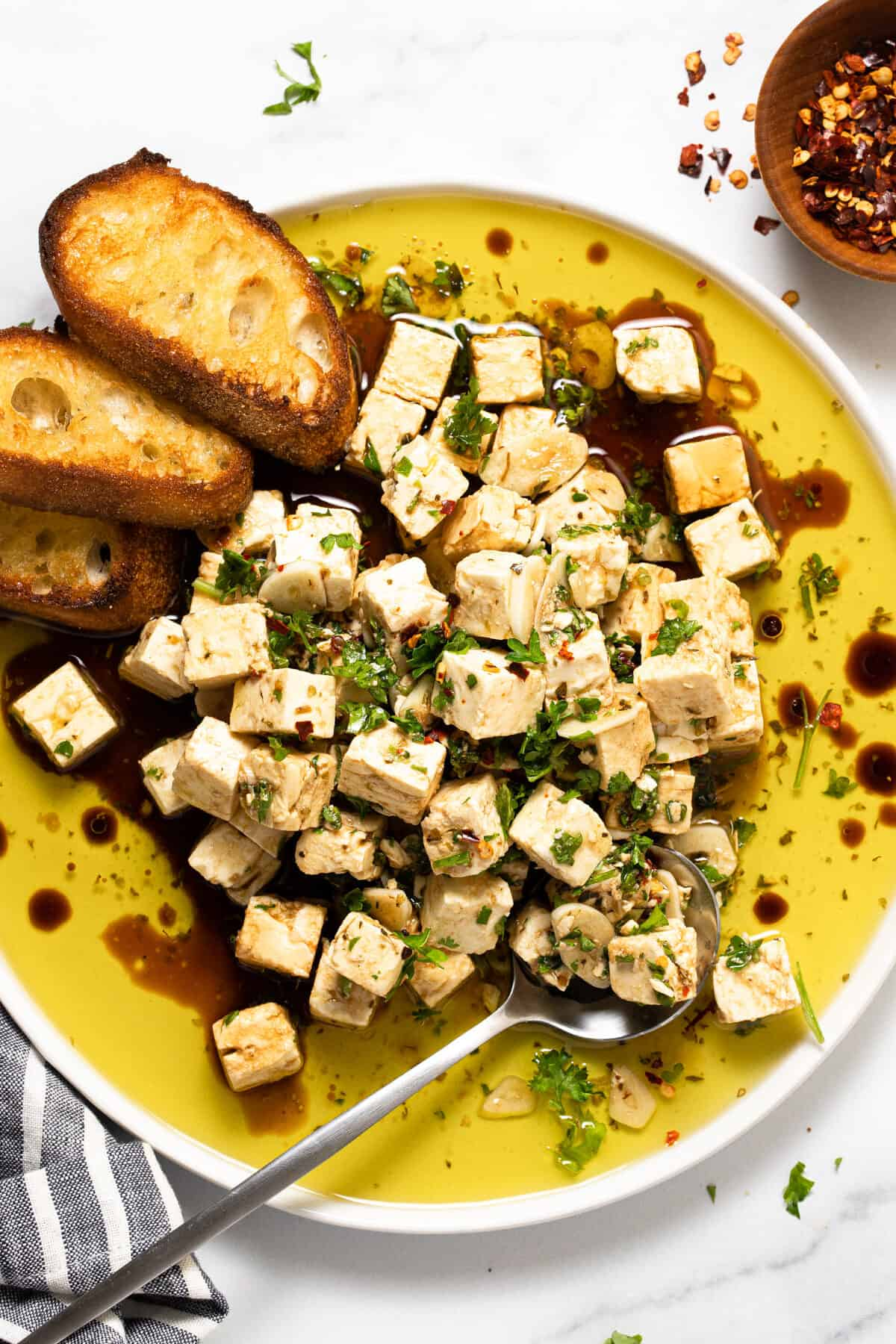 White plate filled with marinated squares of feta with crostini
