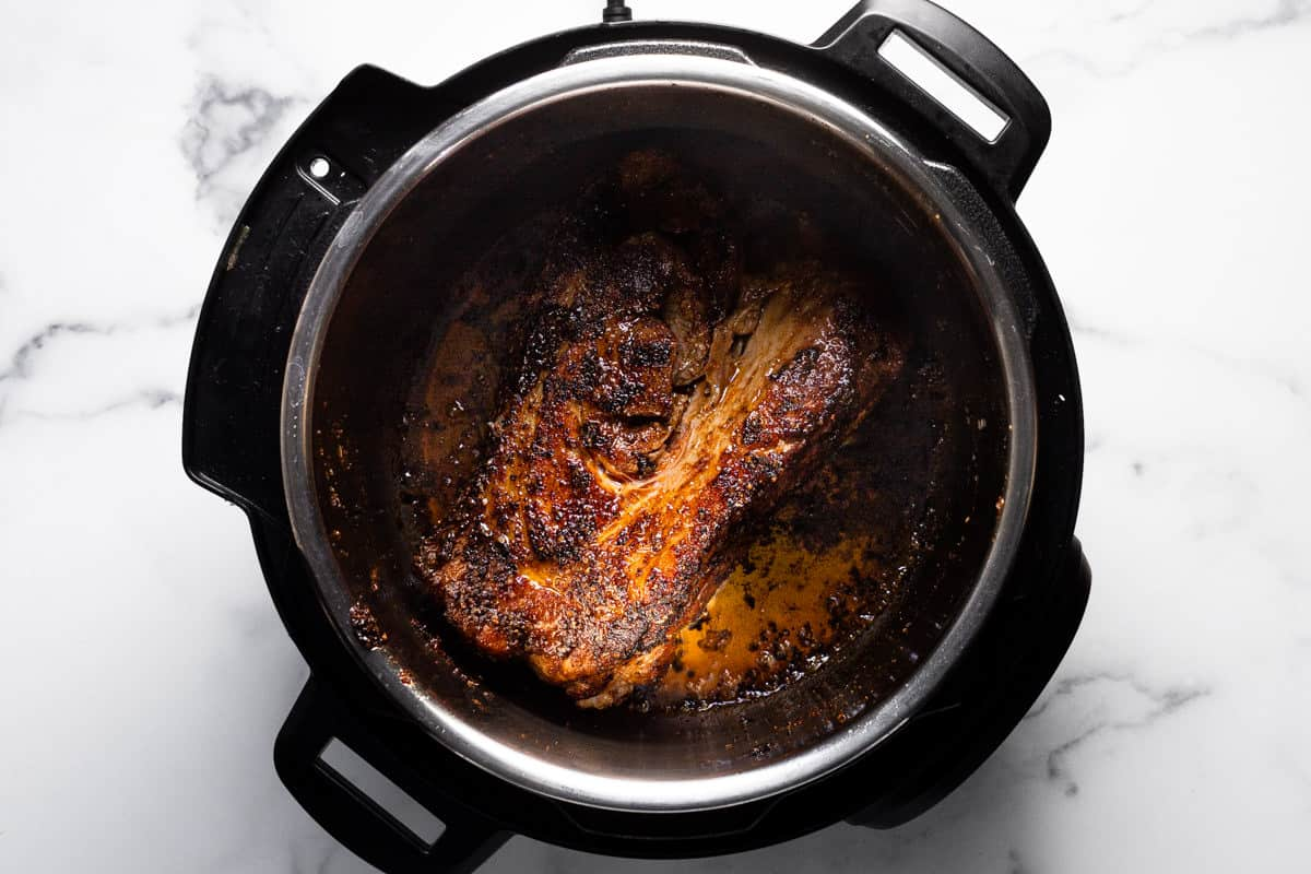 Instant pot filled with ingredients to make BBQ pulled pork