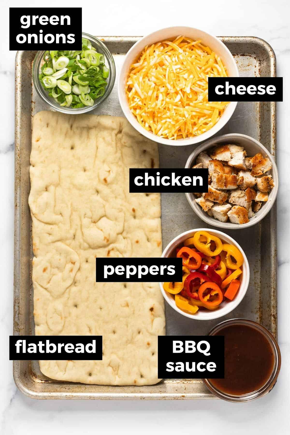 Baking sheet with ingredients to make BBQ chicken flatbread