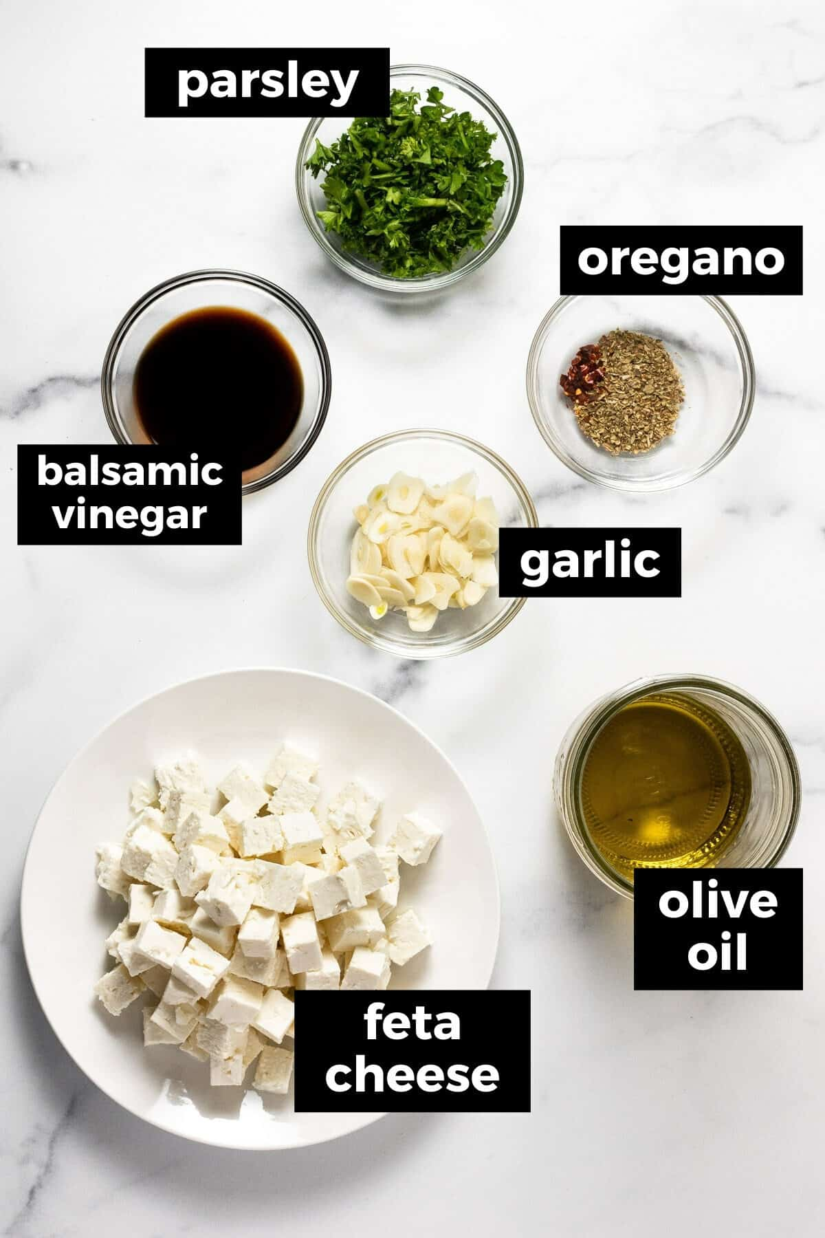White marble countertop filled with ingredients to make marinated feta