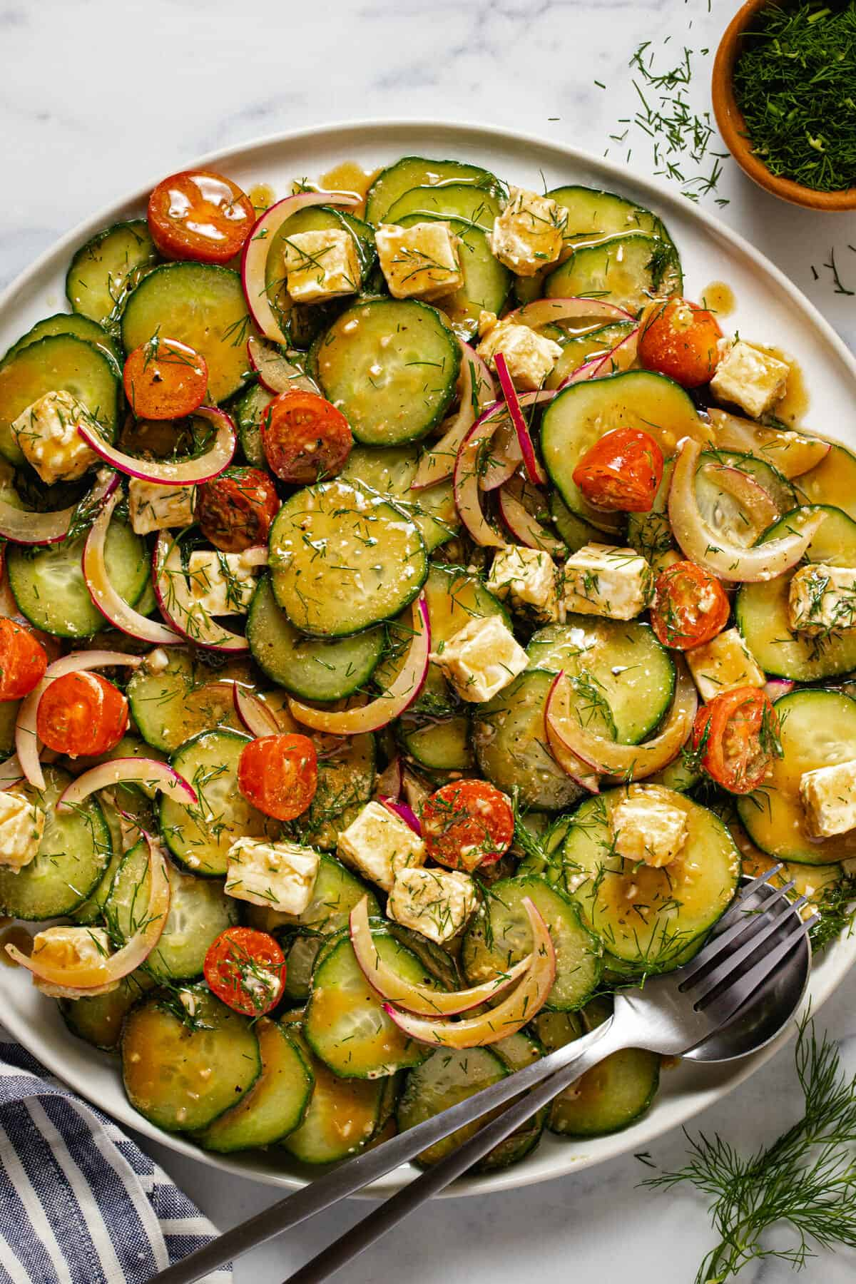 Large white serving platter filled with Mediterranean onion cucumber salad