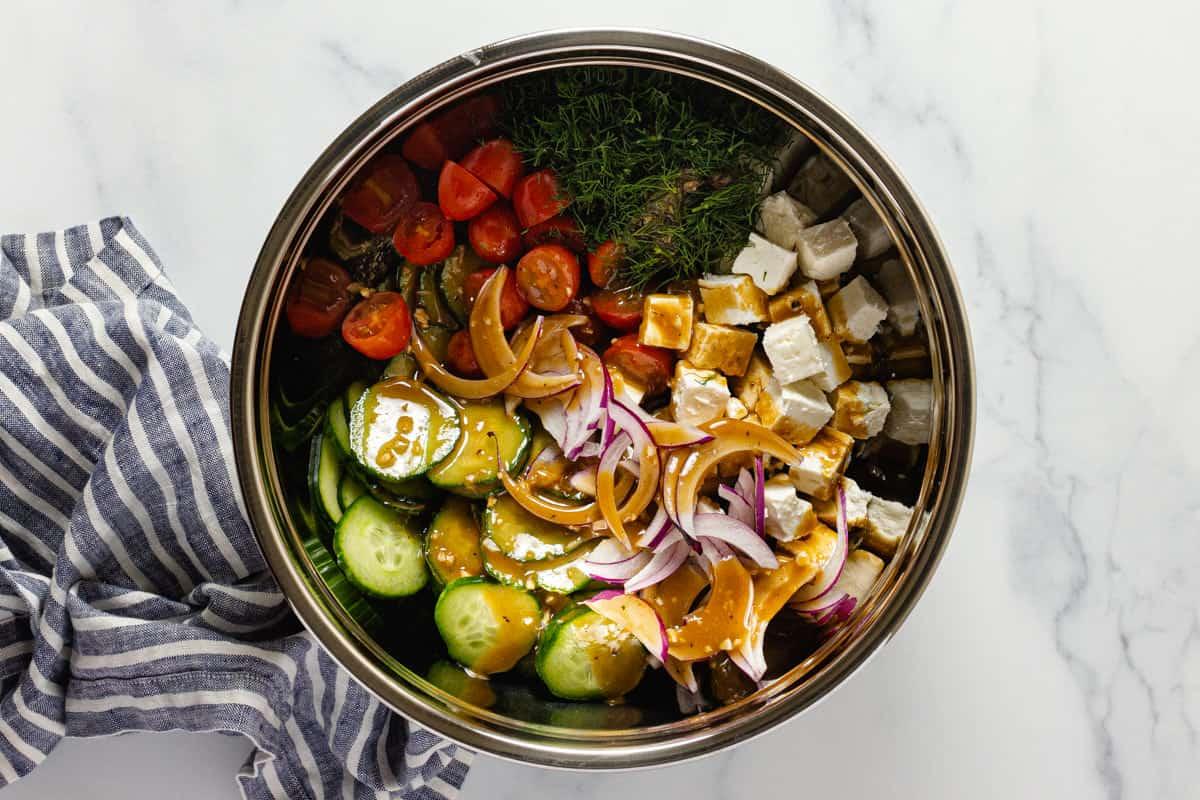 Large metal bowl filled with ingredients to make Greek cucumber salad