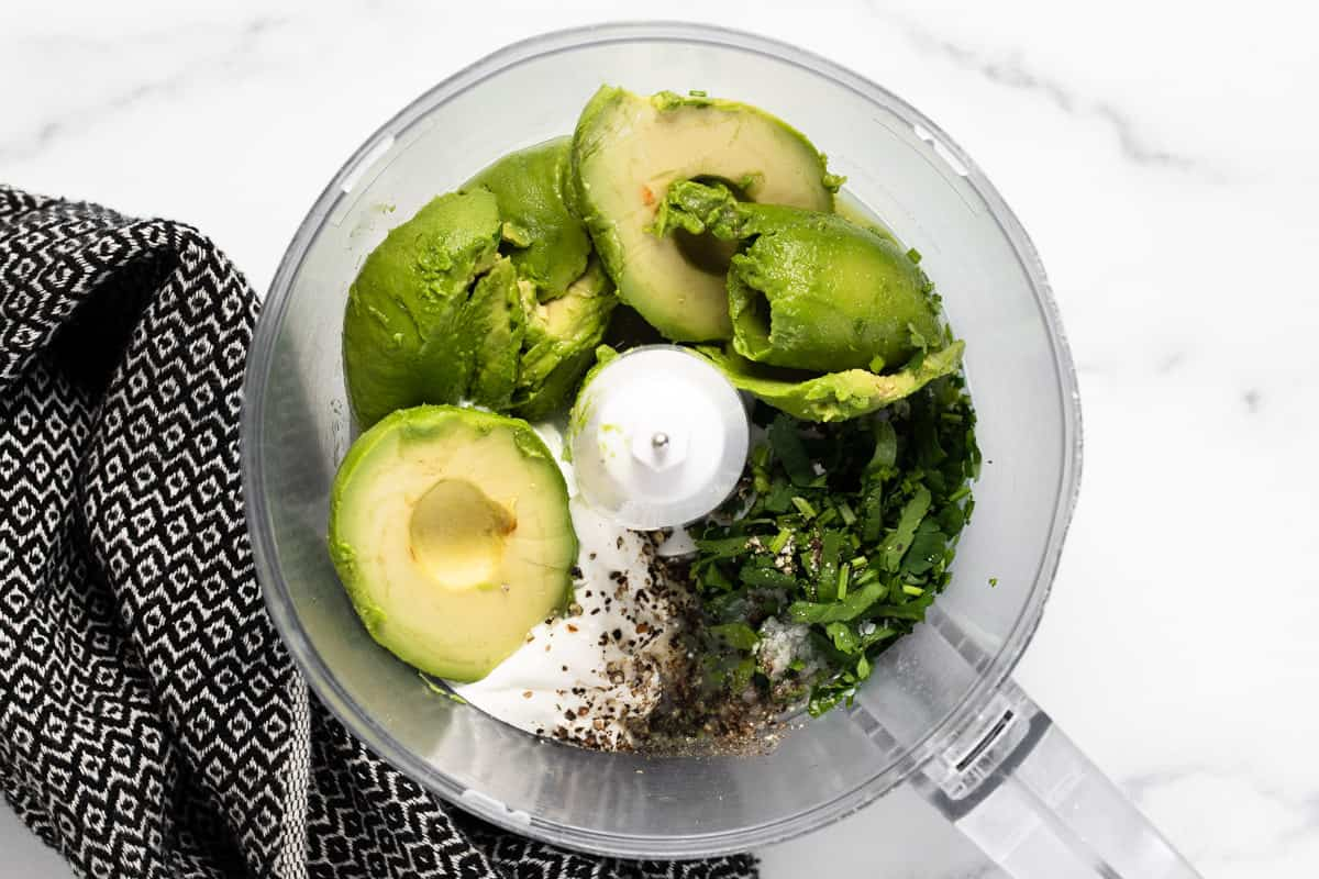 Food processer filled with ingredients to make creamy avocado sauce