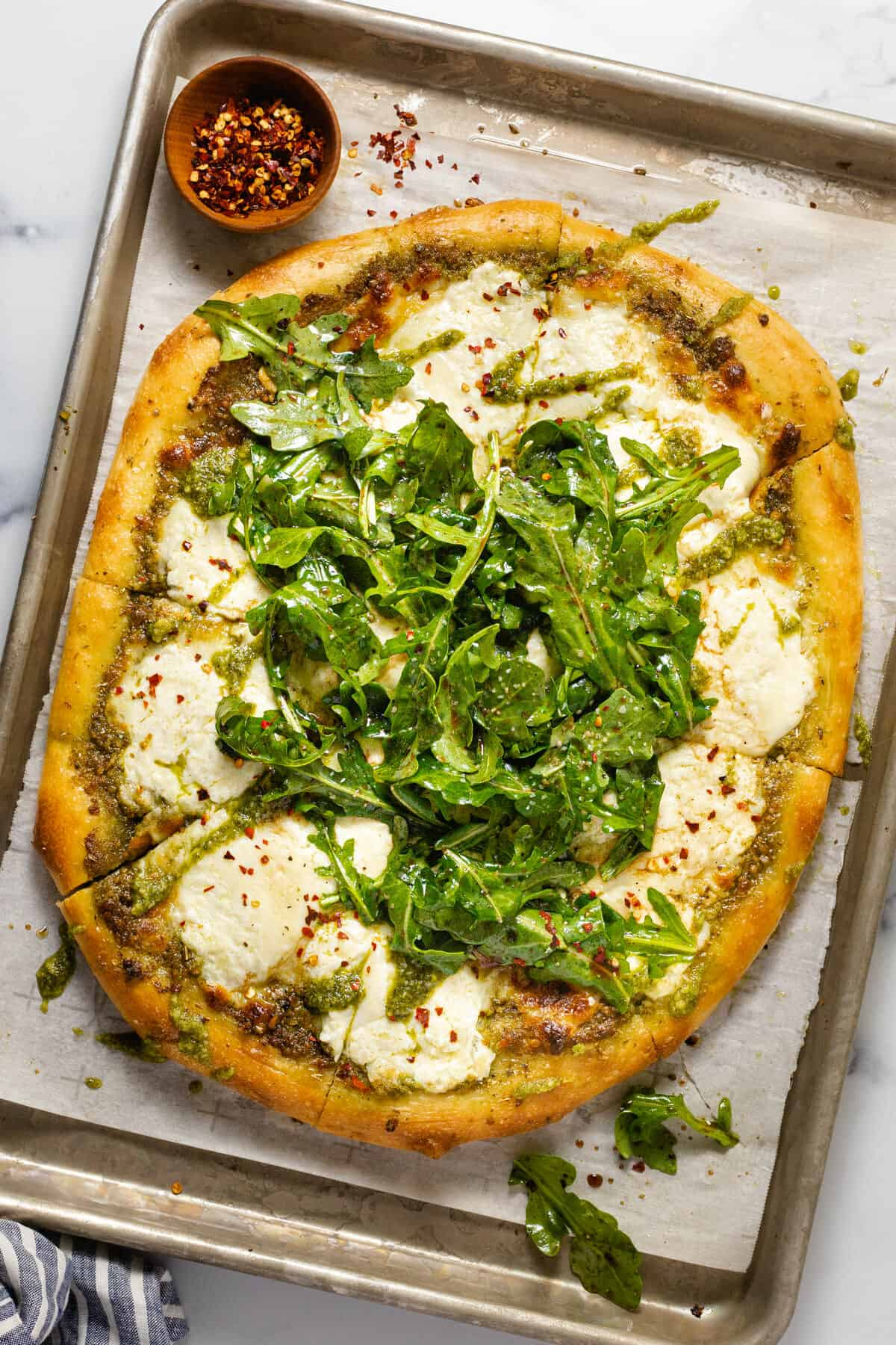 Parchment lined baking sheet with homemade burrata pizza garnished with arugula