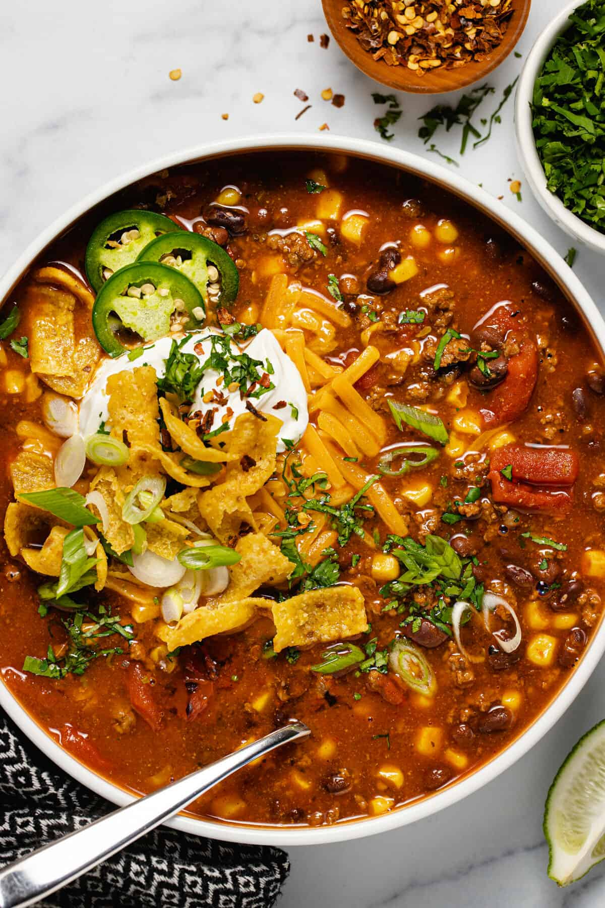 Overhead shot of a white bowl filled with instant pot taco soup garnished with sour cream and cheese