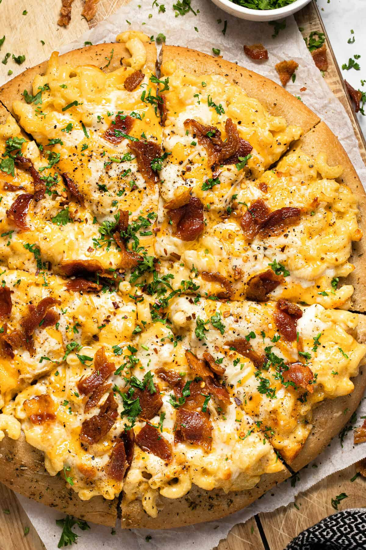 Homemade mac and cheese pizza on a wooden cutting board