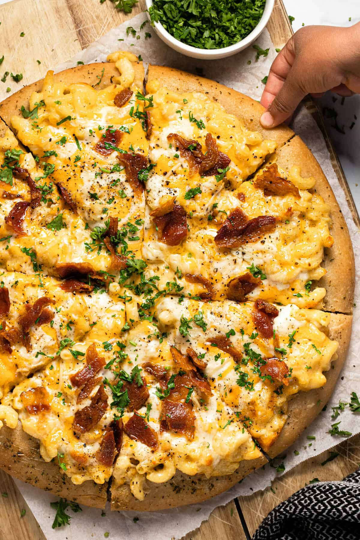 A hand reaching for a slice of mac and cheese pizza with bacon