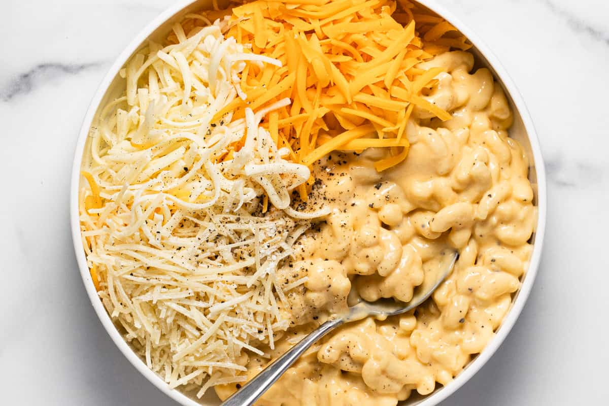 White bowl filled with mac and cheese and shredded cheese
