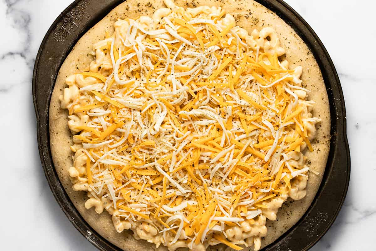 Mac and cheese pizza on a pizza pan just before baking it