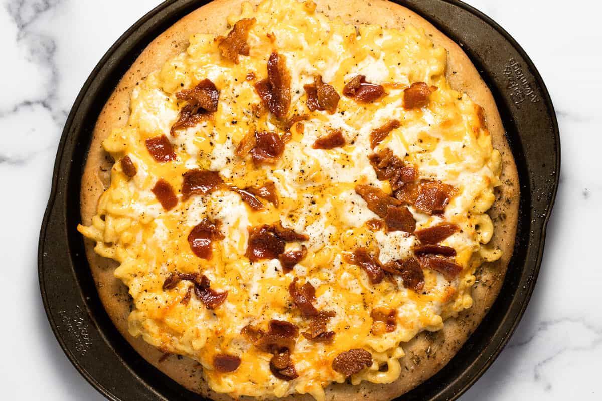 Freshly baked mac and cheese pizza with crumbled bacon