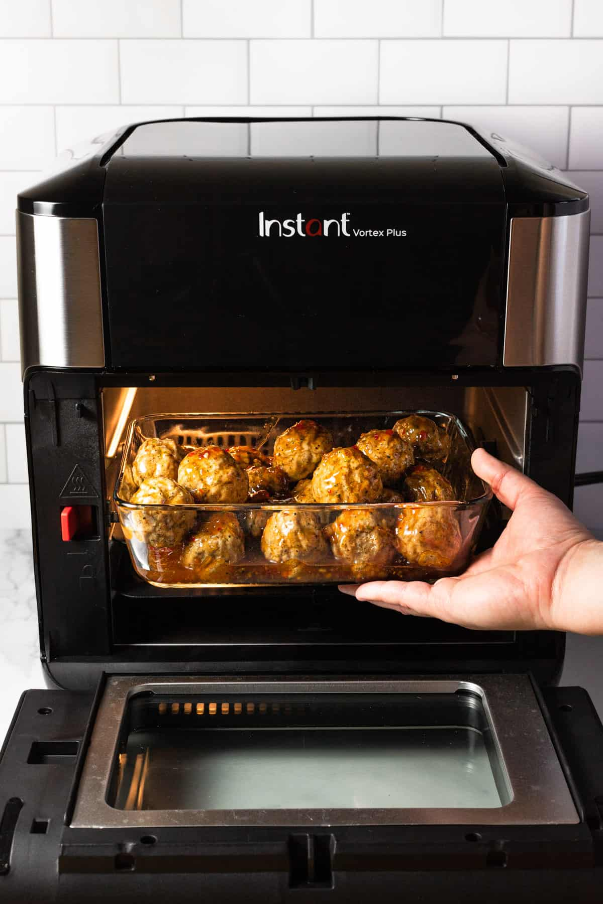 A hand putting a glass baking dish of meatballs into a small oven