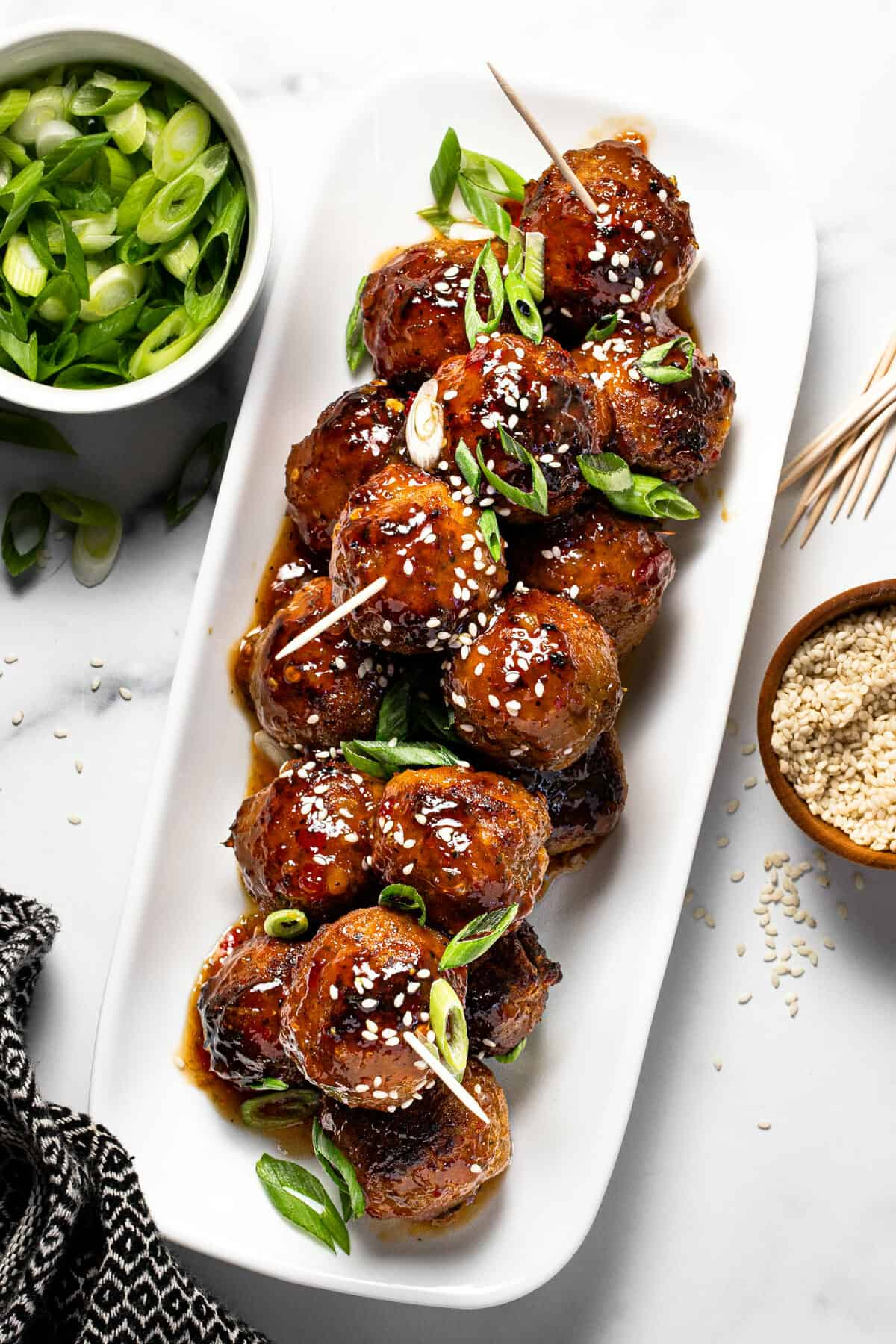 White platter filled with glazed meatballs garnished with green onion