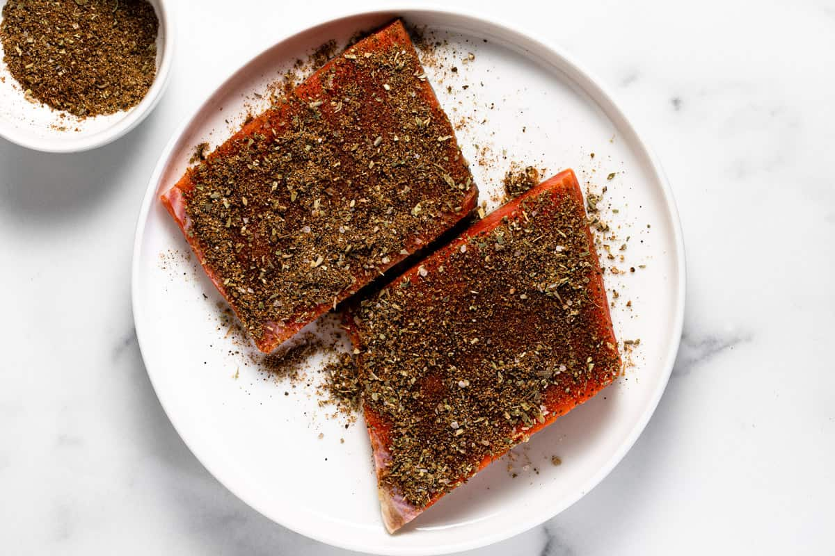 White plate with seasoned salmon filets