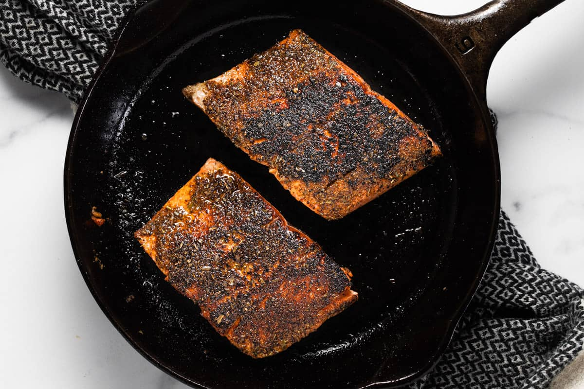 Cast iron pan with blackened salmon for tacos