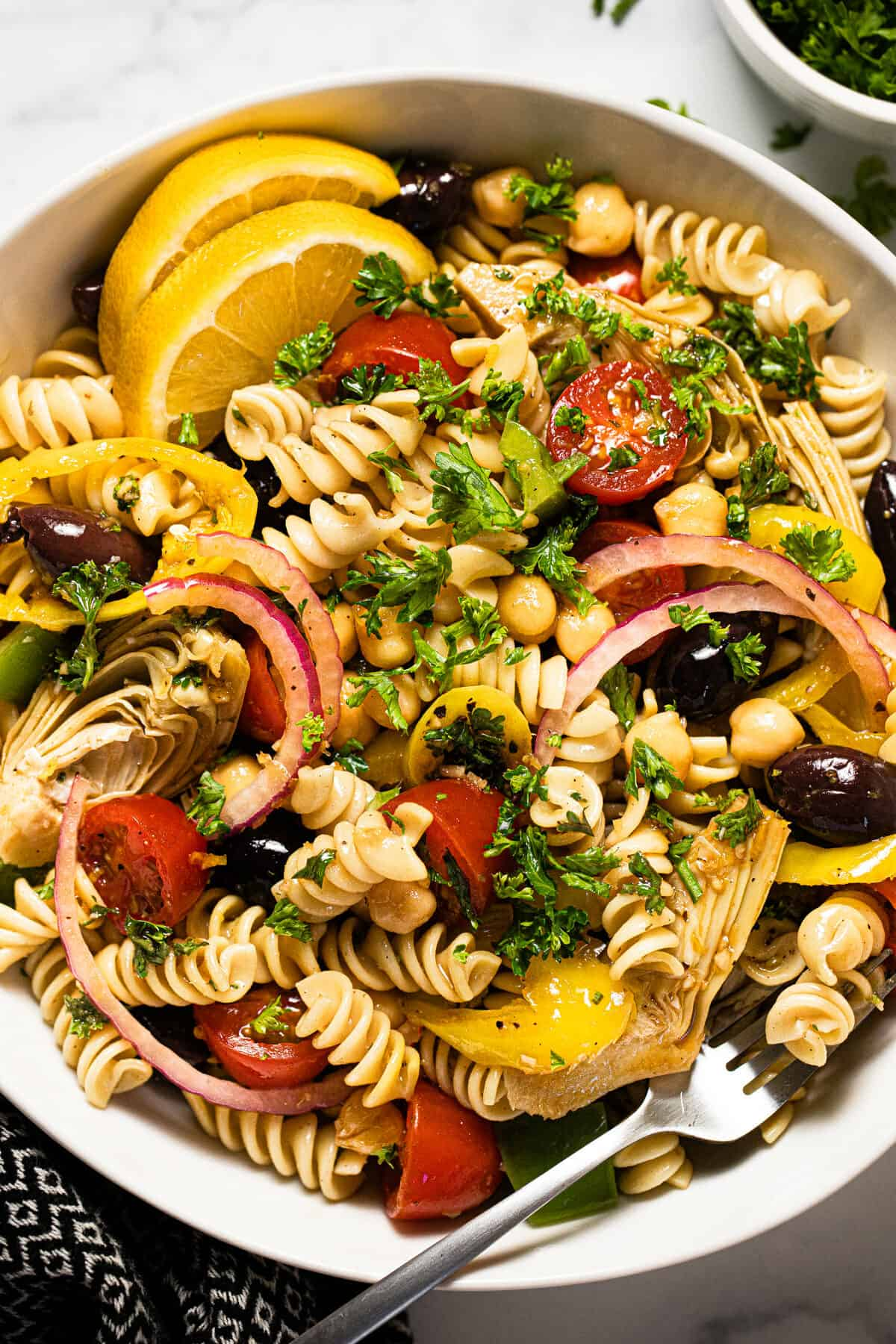 Overhead shot of a bowl of vegan pasta salad garnished with chopped parsley