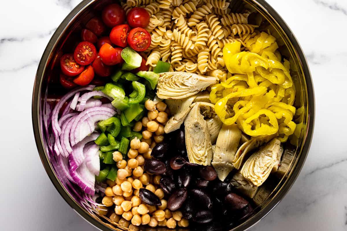 Large metal bowl filled with ingredients to make vegan pasta salad
