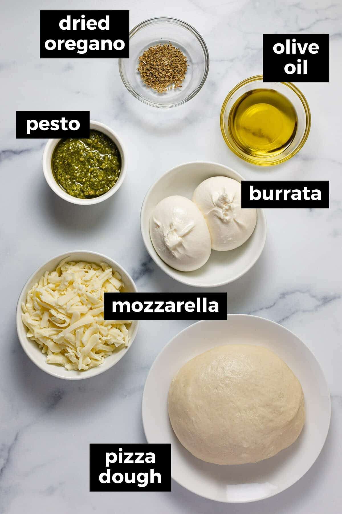 White marble counter top with bowls of ingredients to make burrata arugula pizza