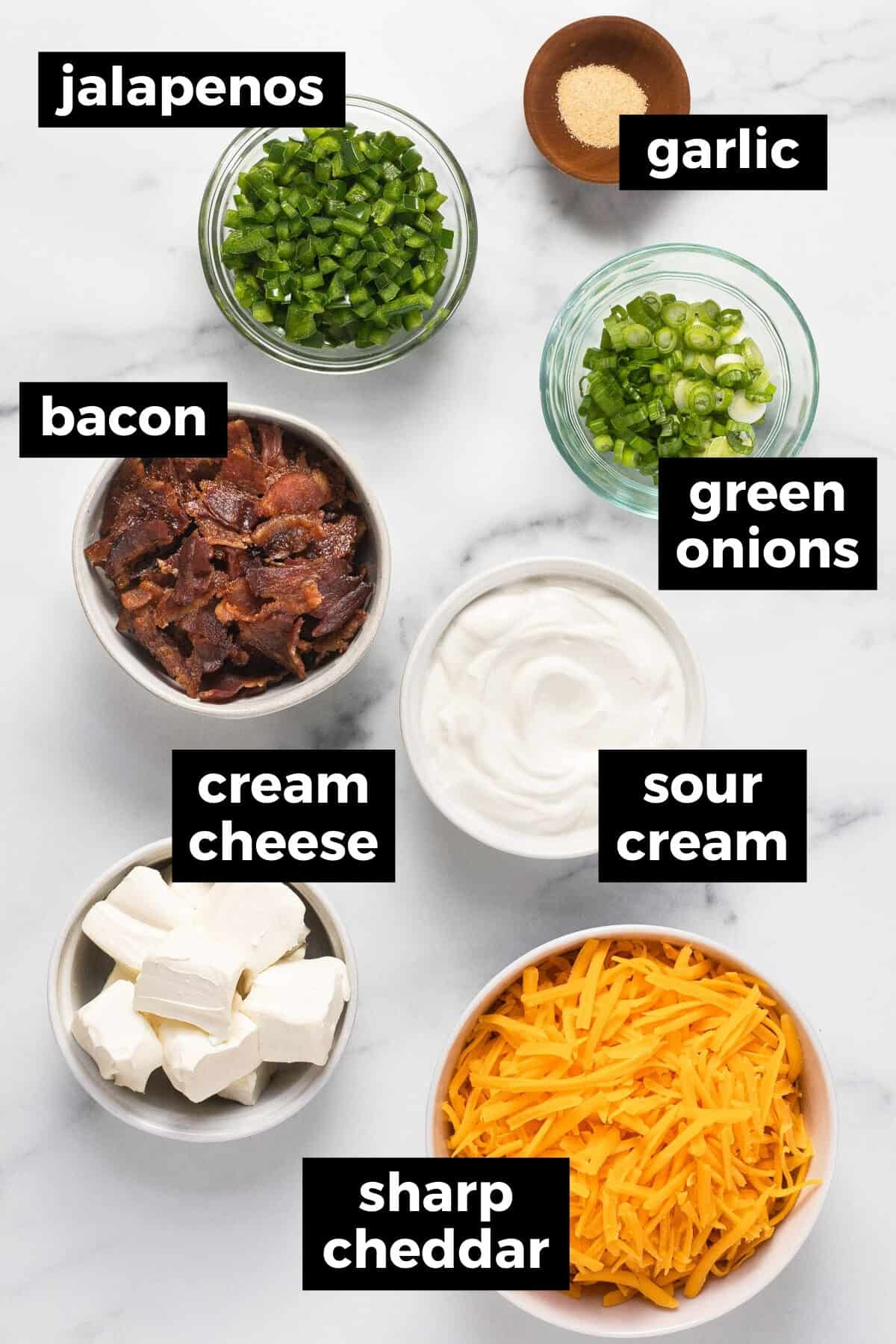 White marble counter top with ingredients to make jalapeno popper dip
