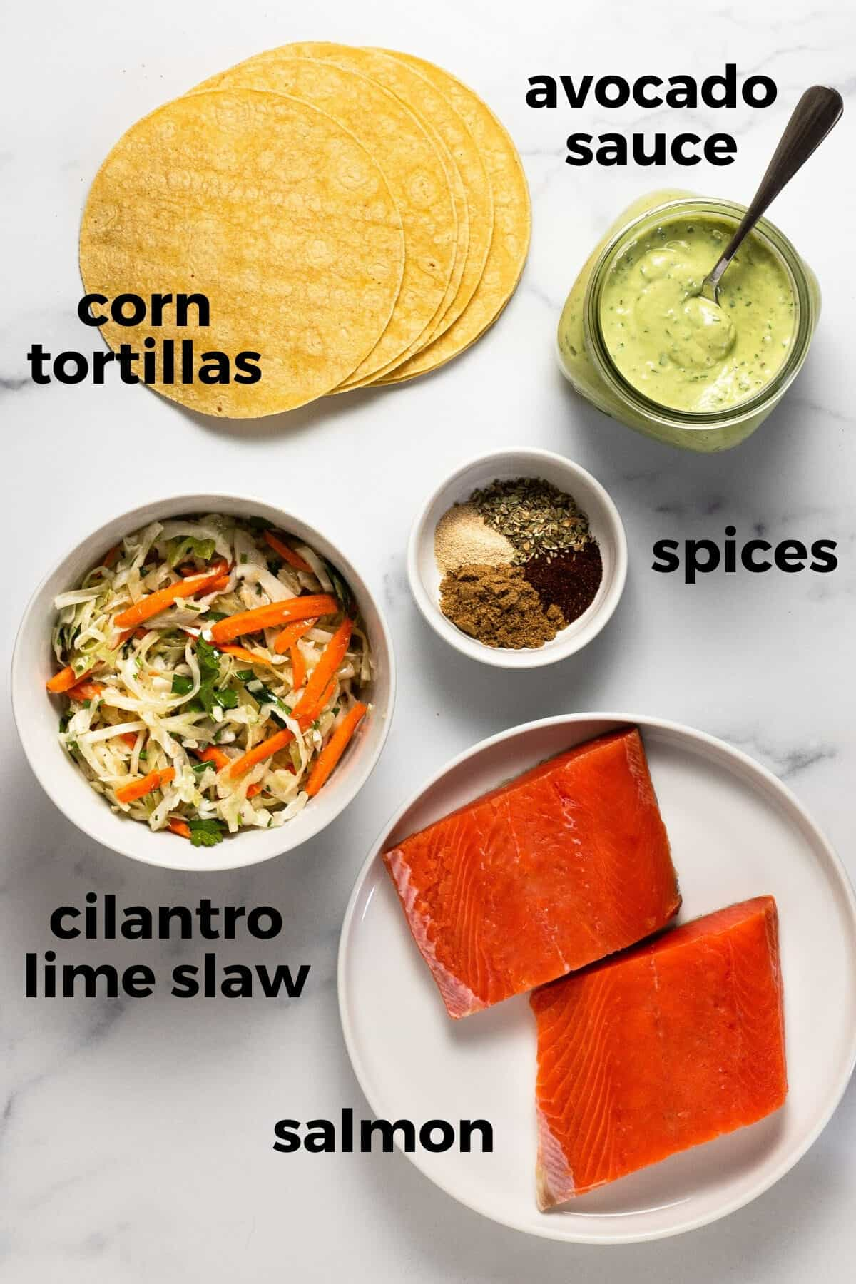 White marble counter top with ingredients to make a salmon taco recipe