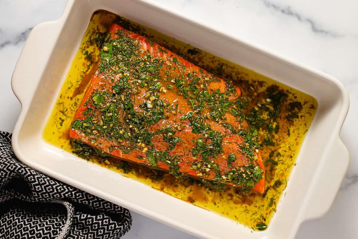 Large white baking dish filled with marinated salmon