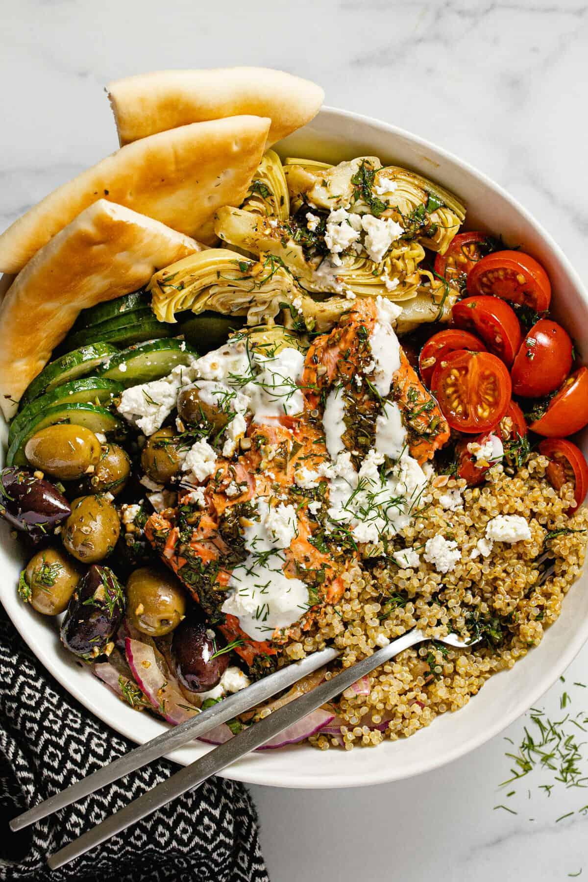 Large white bowl filled with Mediterranean salmon veggies and quinoa