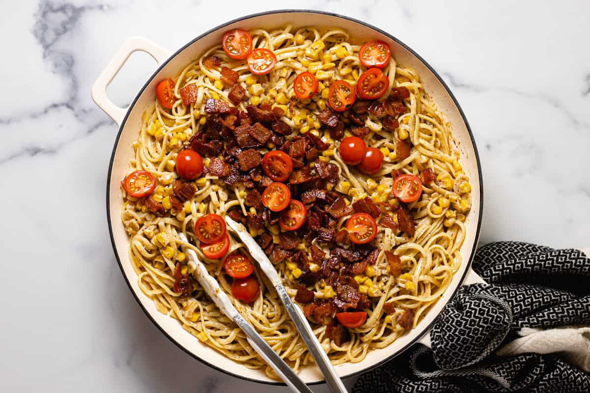Large sauté pan filled with creamy bacon pasta topped with tomatoes