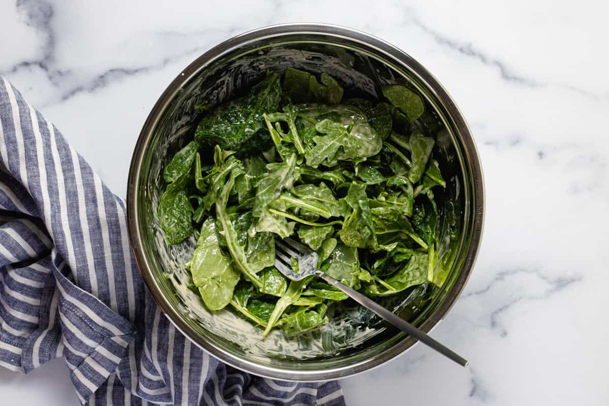 Large metal bowl filled with greens tossed in honey mustard dressing
