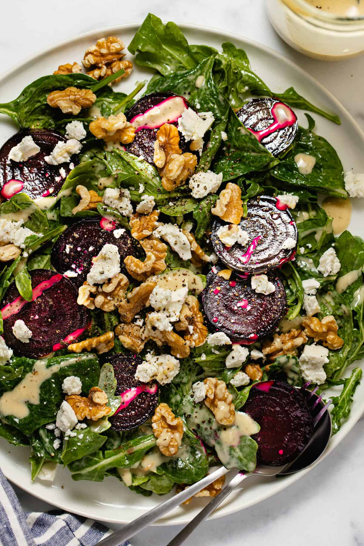 Overhead shot of a white plate filled with beet salad with feta and walnuts