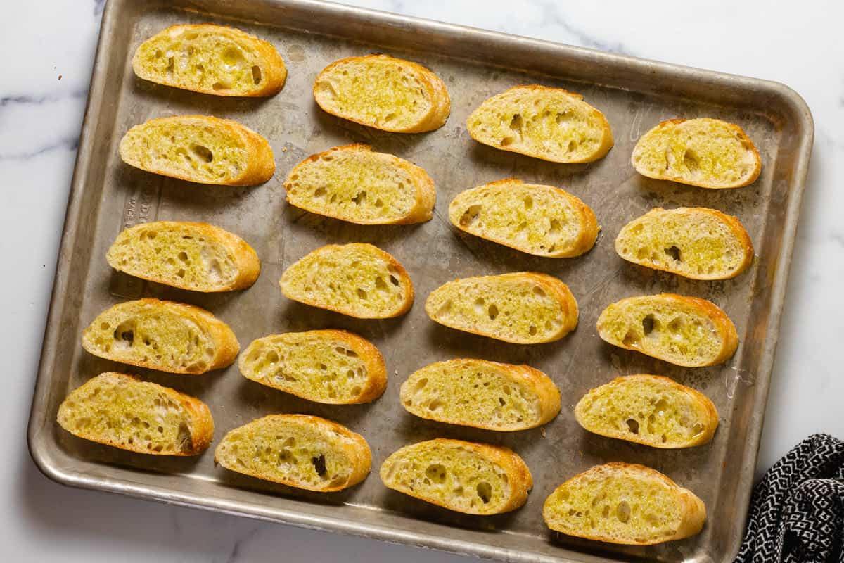 Metal pan filled with sliced French bread brushed with olive oil