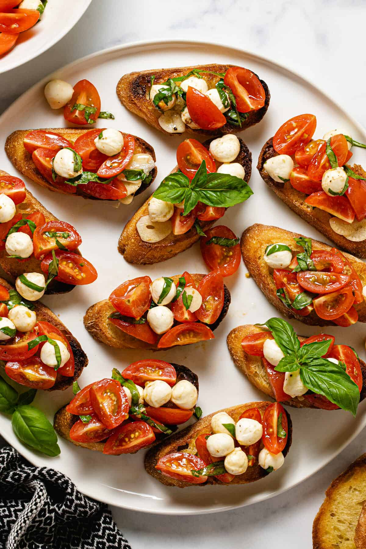 White plate filled with tomato bruschetta garnished with fresh basil