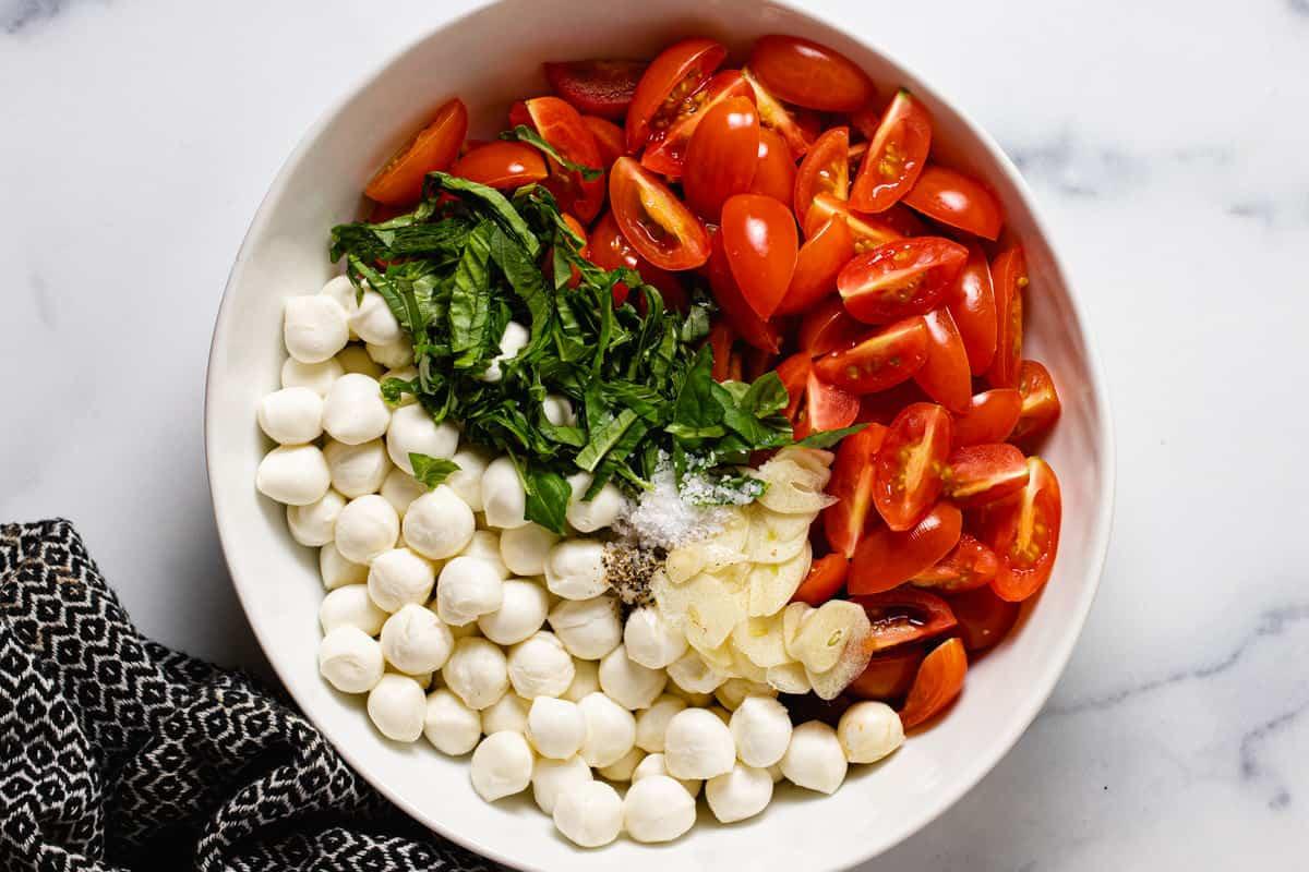 White bowl filled with ingredients to make tomato bruschetta with mozzarella