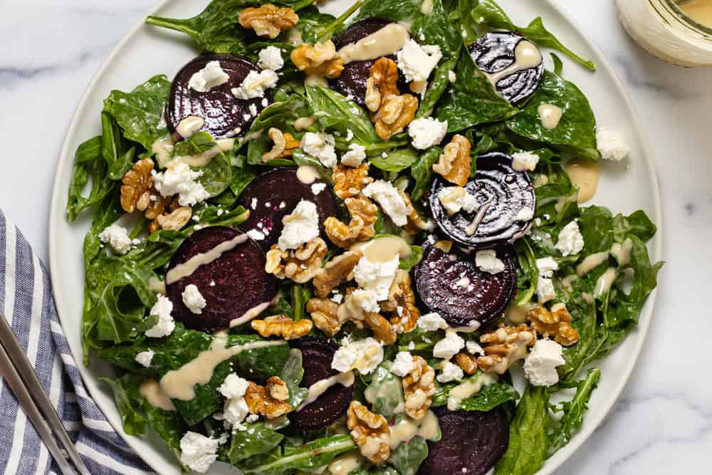 Overhead shot of a roasted beet and feta salad with walnuts and honey mustard dressing