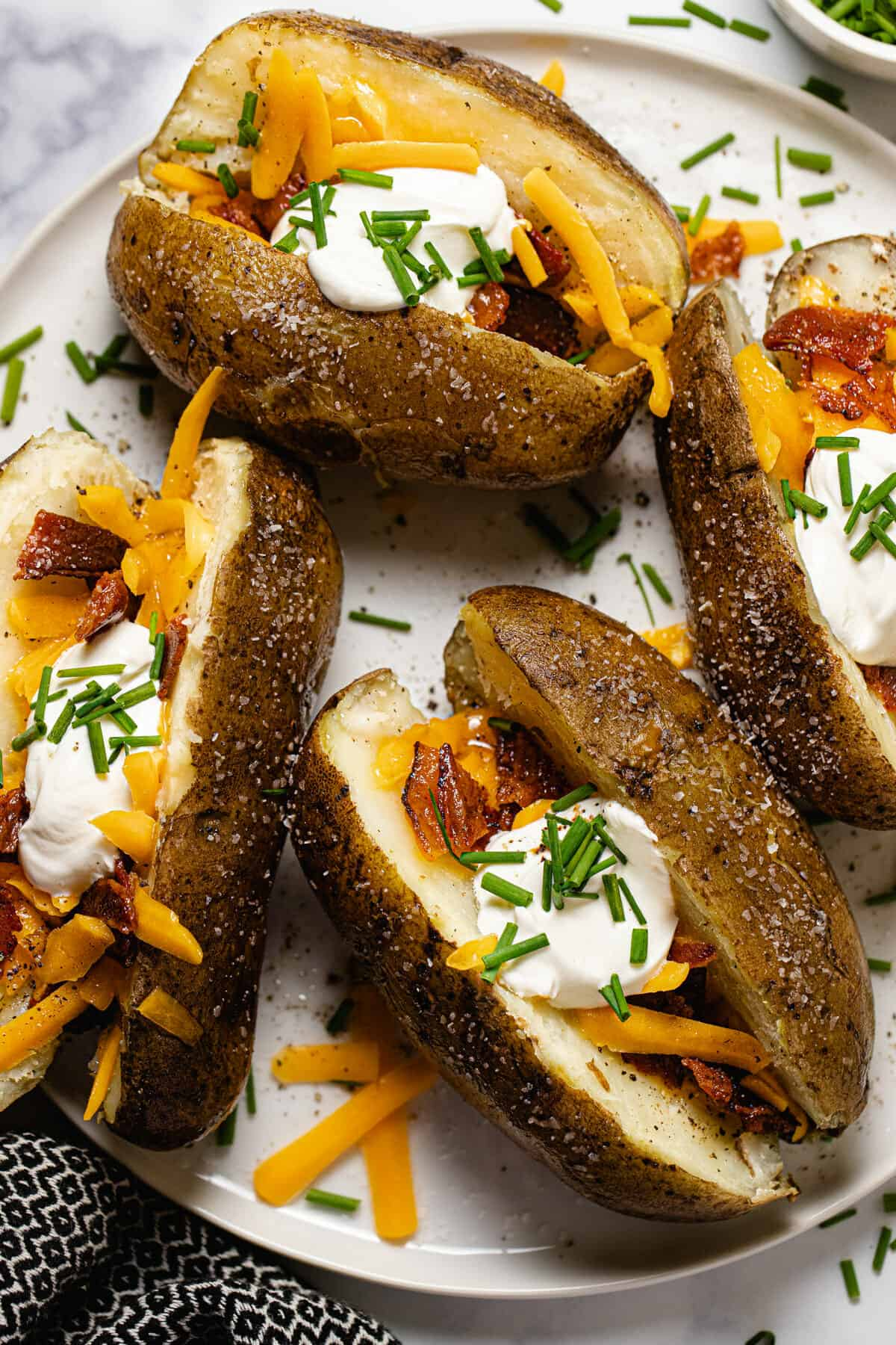 White plate with four loaded baked potatoes garnished with chives