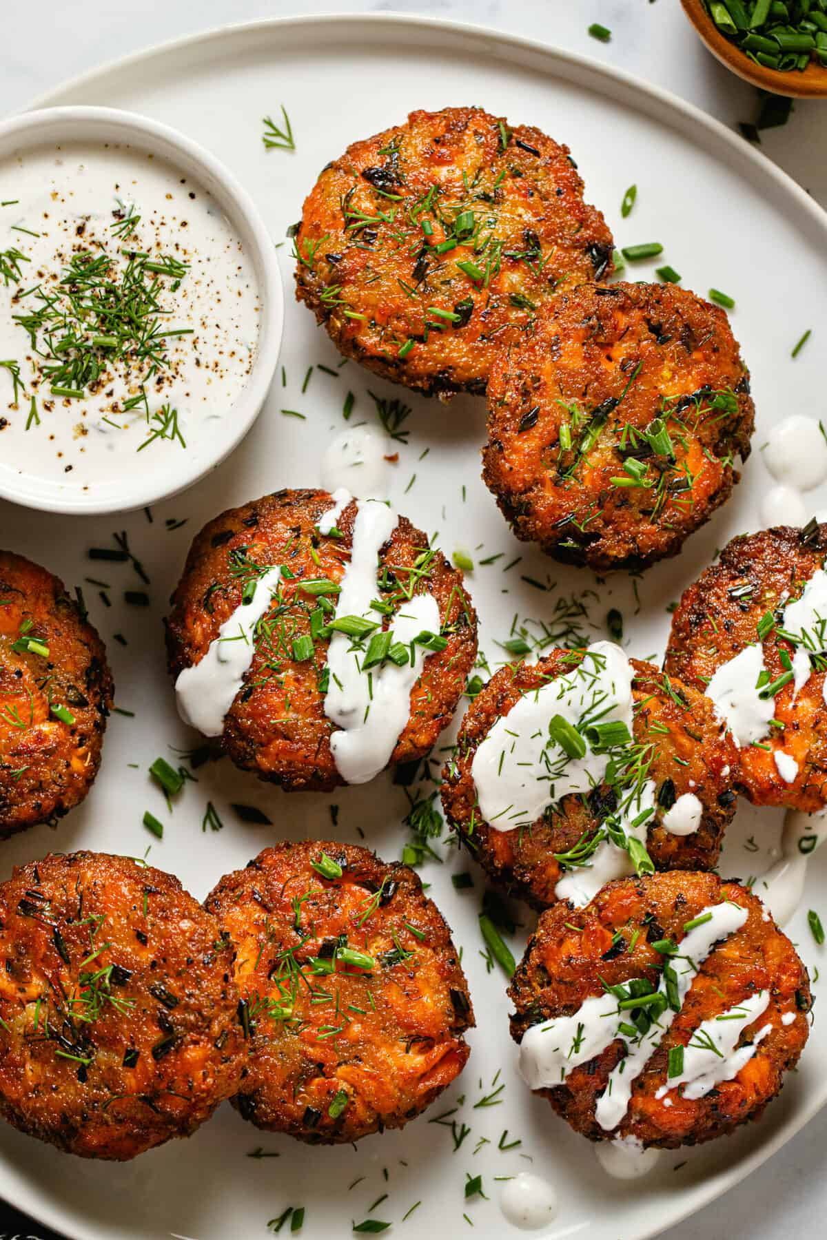 White plate filled with homemade salmon cakes garnished with fresh dill