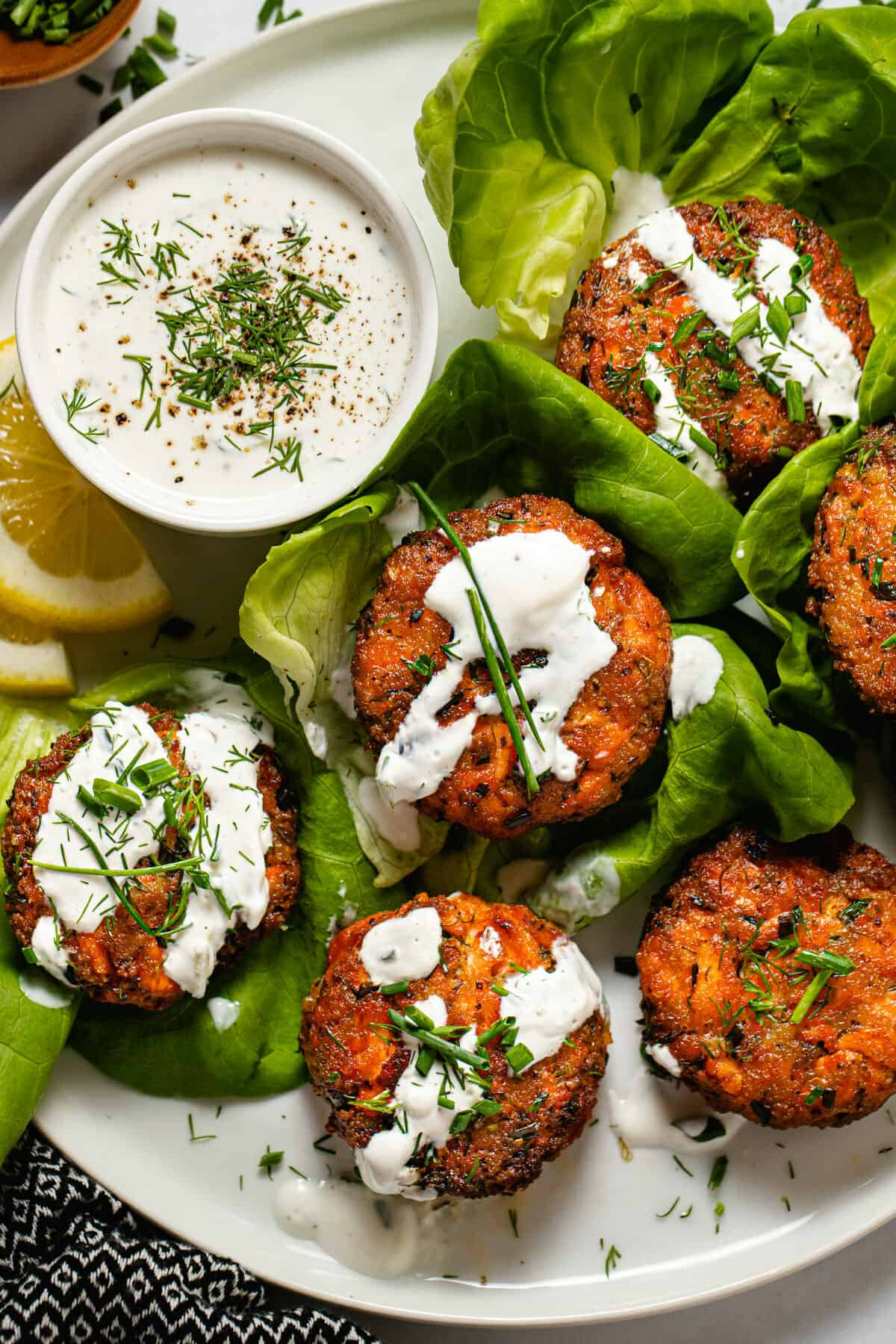 White plate with salmon patties wrapped in lettuce drizzled with tzatziki