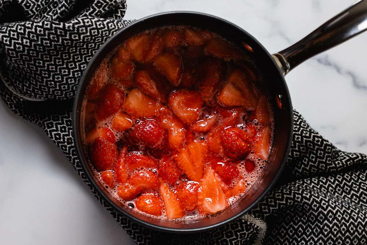 Medium saucepan filled with ingredients to make strawberry compote