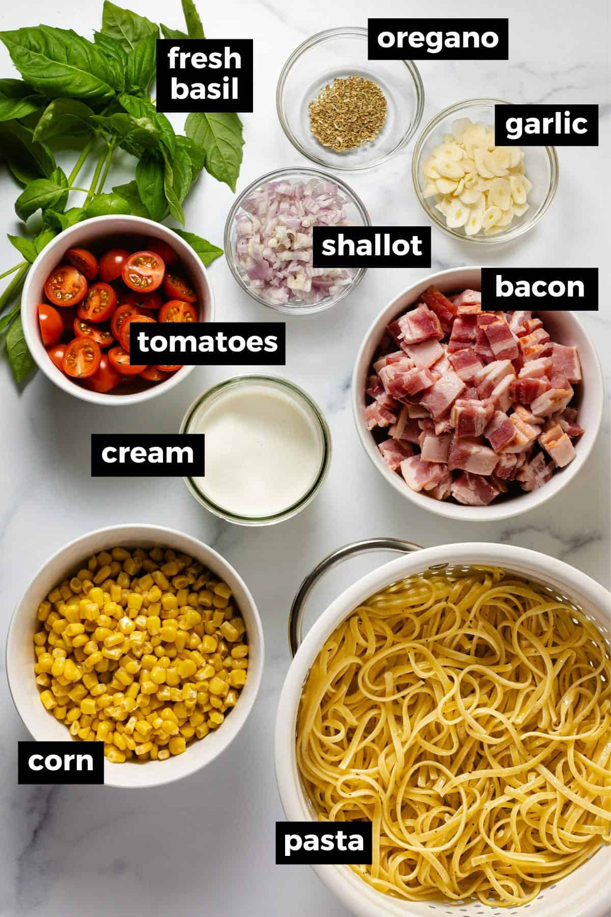 White marble counter top with bowls of ingredients to make creamy corn pasta