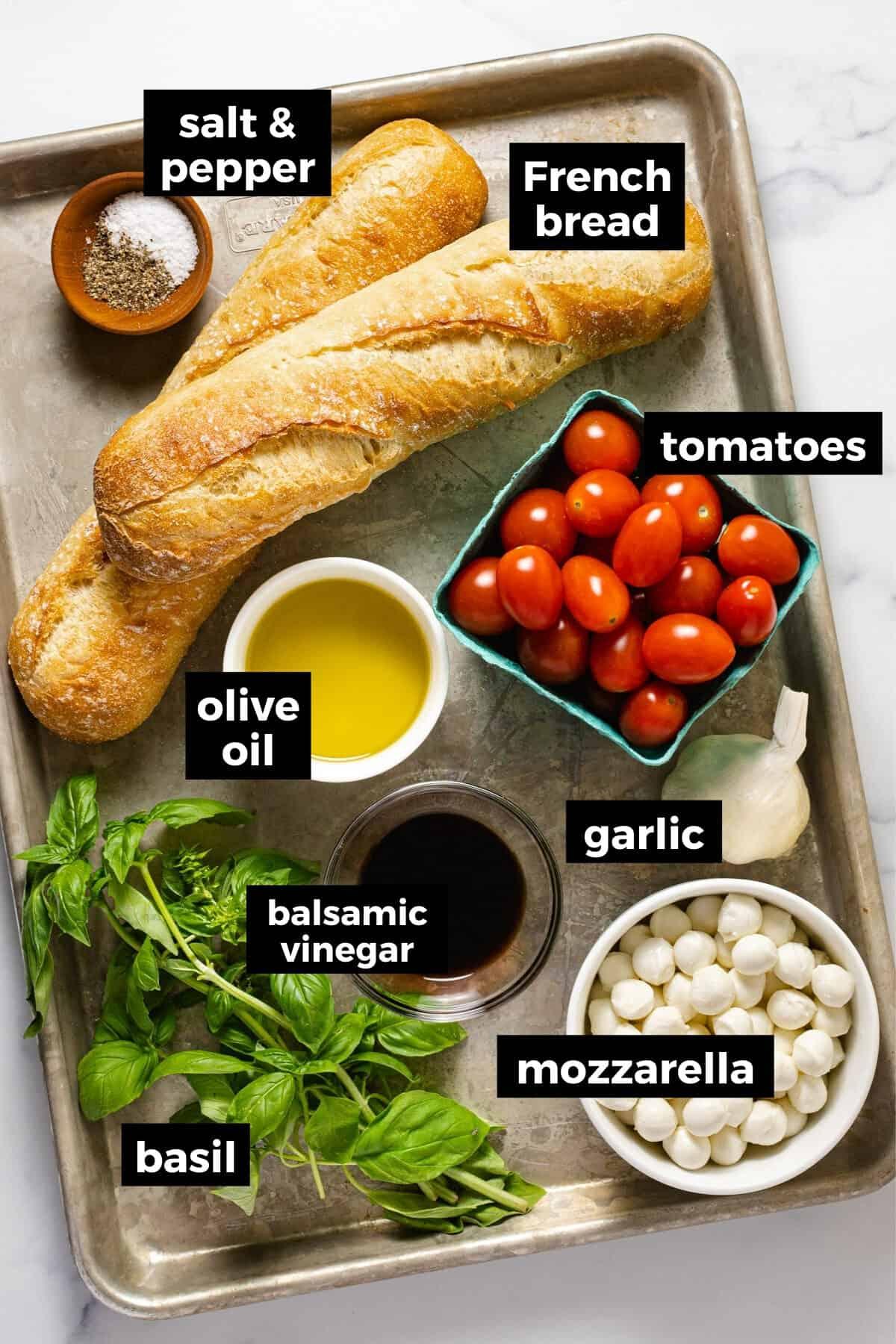 Metal sheet pan with ingredients to make bruschetta with mozzarella