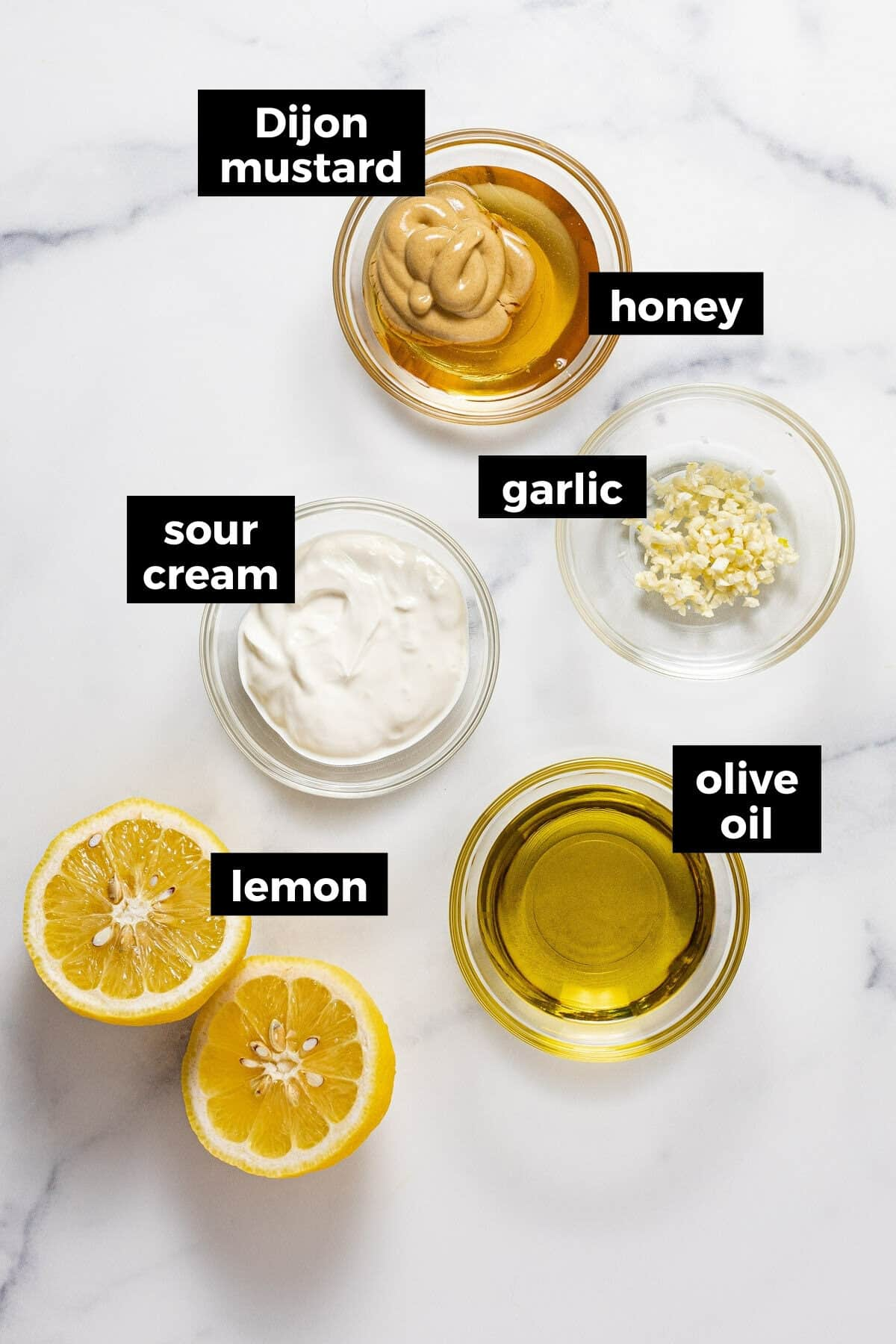 White marble counter top with ingredients to make honey mustard dressing