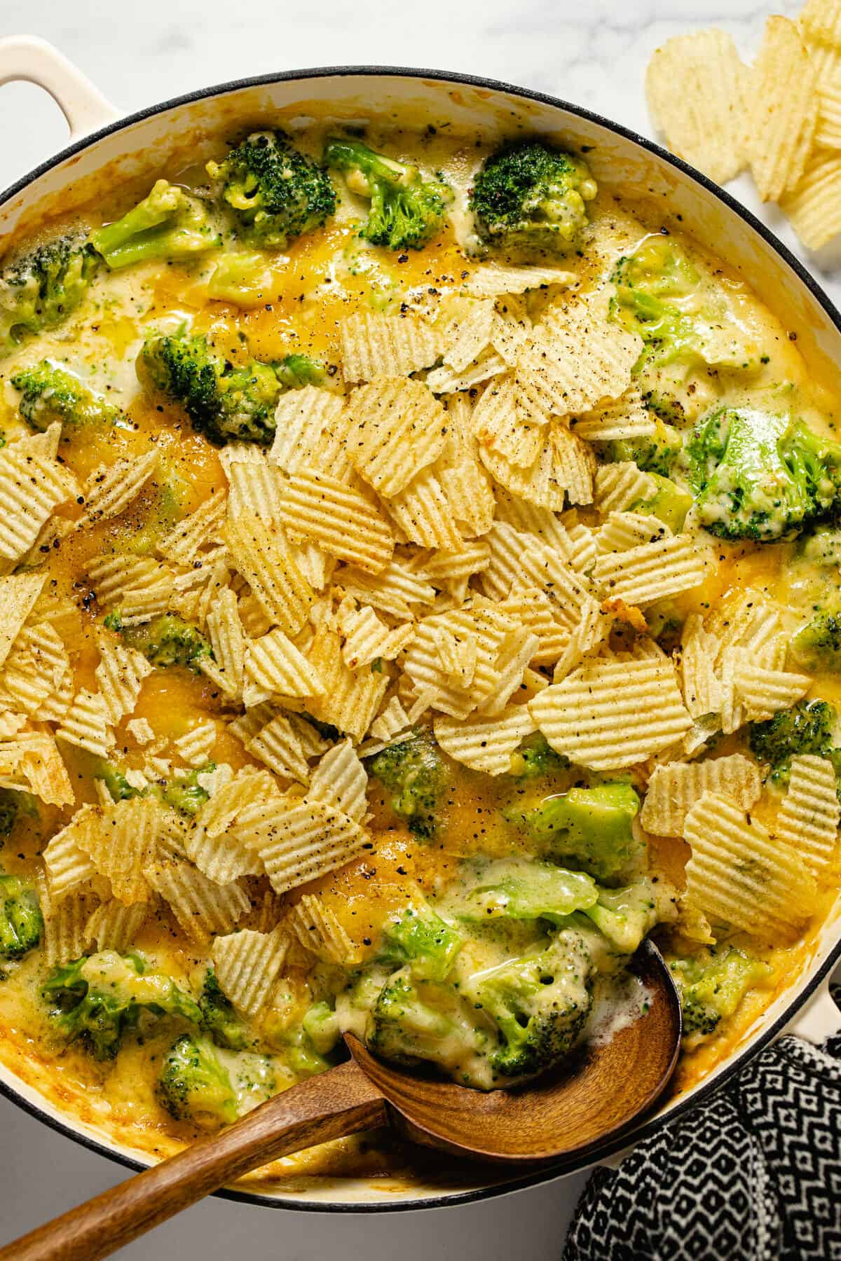 Overhead shot of a large white pan filled with broccoli cheese casserole topped with potato chips