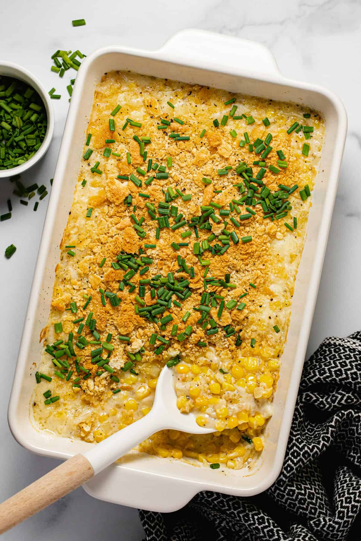 Overhead shot of a white baking dish filled with creamy corn casserole