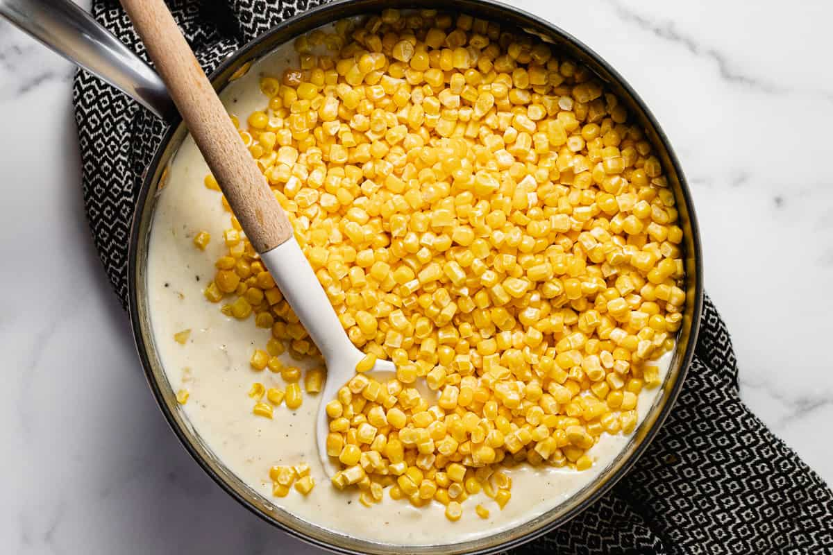 Large pan filled with frozen corn in a creamy cheese sauce