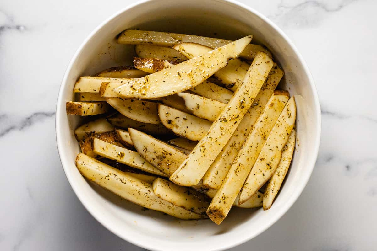 White bowl filled with raw potatoes cut into fries olive oil and seasonings