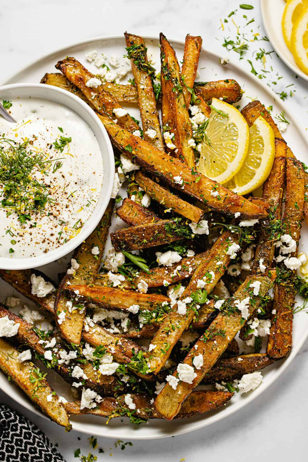 Large white plate filled with homemade Greek fries and a bowl of dill yogurt sauce