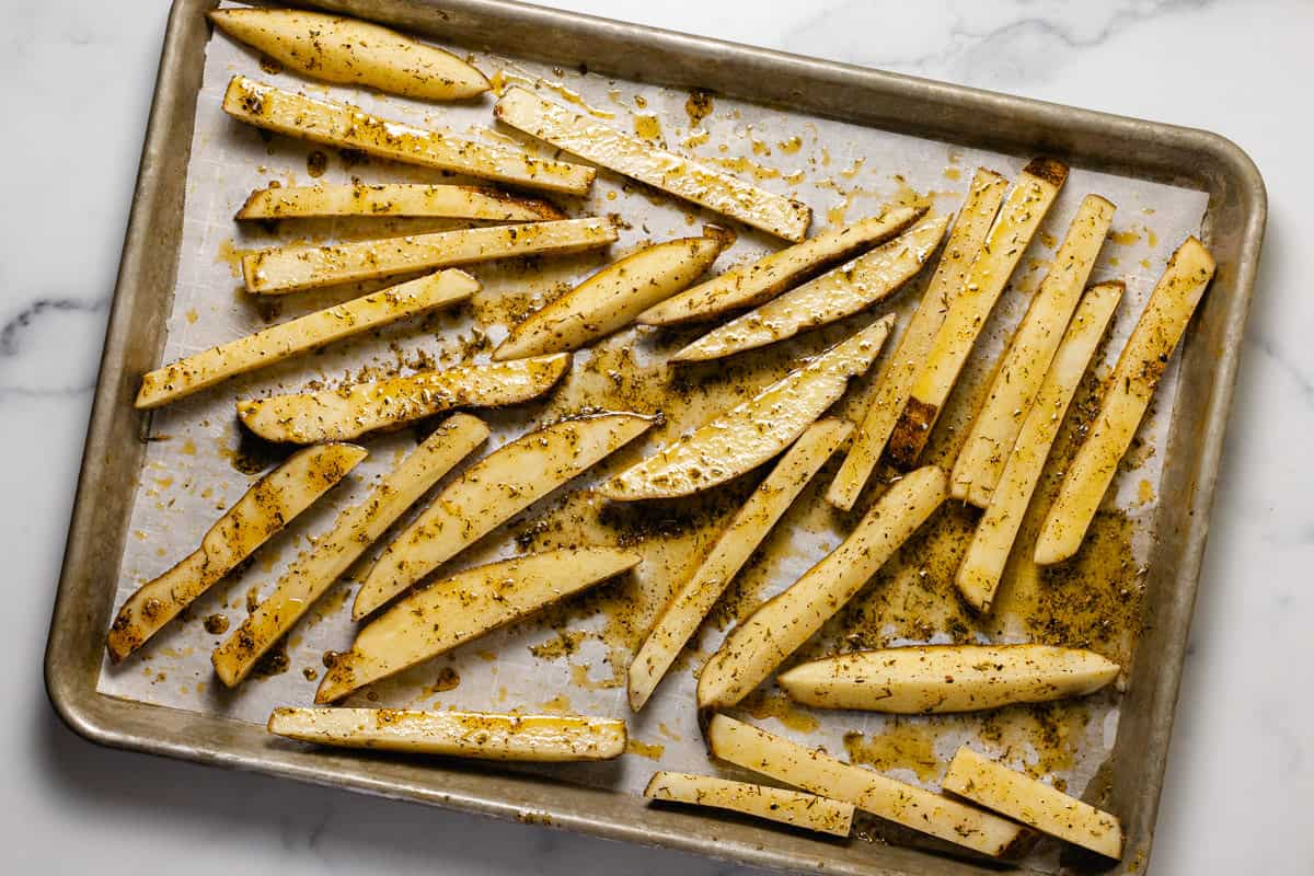 Raw French fries on a parchment lined baking sheet ready to go in the oven
