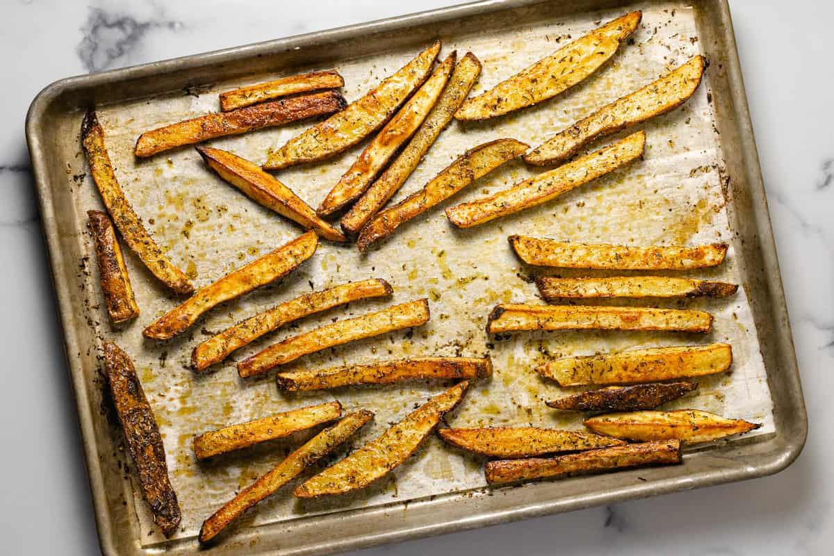 Freshly baked French fries on a parchment lined baking sheet
