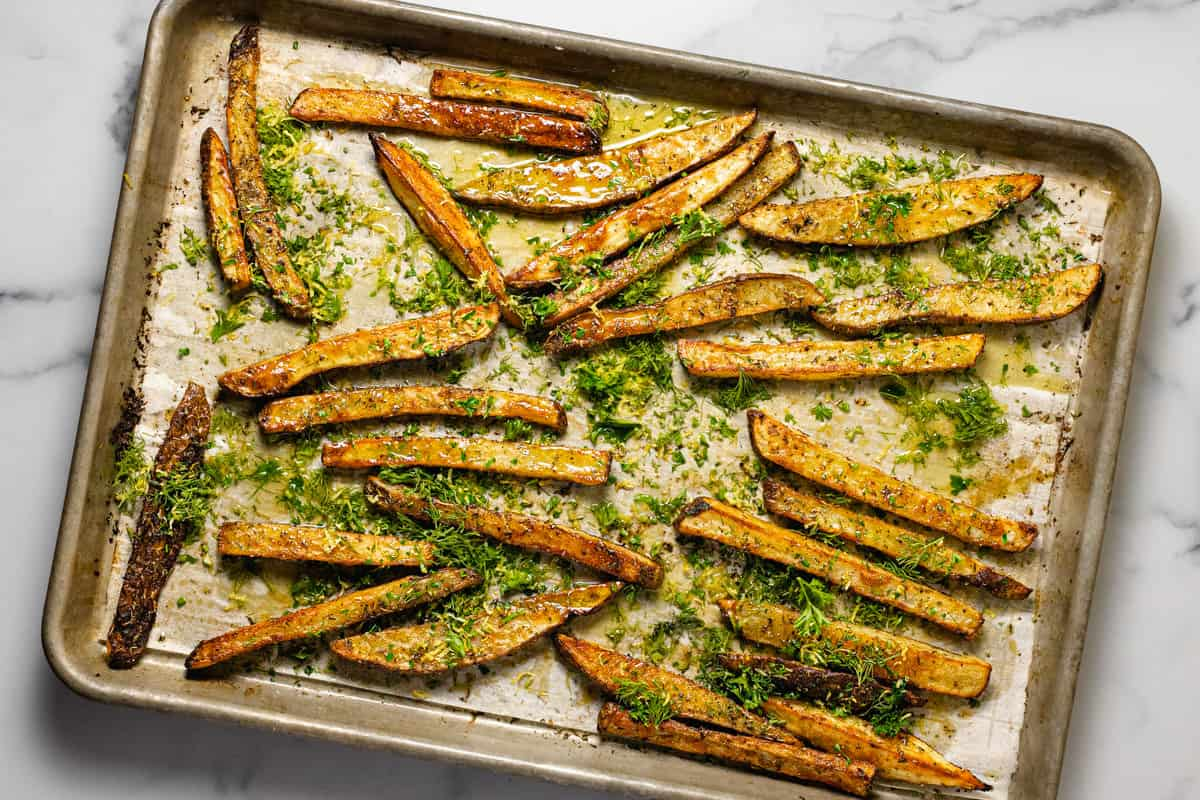 Homemade baked Greek fries on a parchment lined baking sheet topped with fresh herbs and lemon zest
